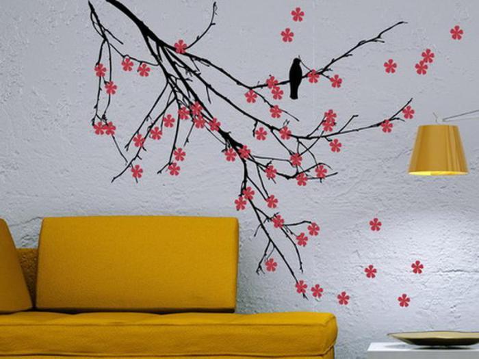 Комната с комбинированным интерьером. На фоне серой стены нарисовано дерево с яркими цветами, в дополнении с желтым диваном.
