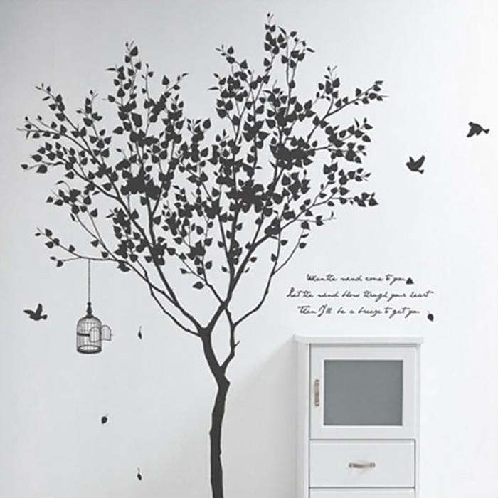 Комната выполнена в черно-белой цветовой гамме с симпатичным деревом на стене.