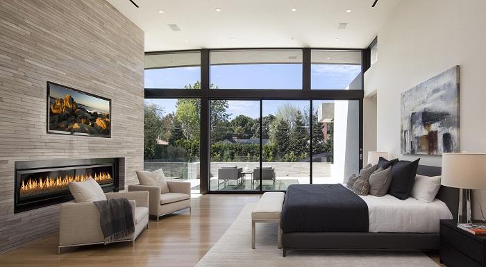 Домашняя обстановка в спальне создана благодаря камину и современному интерьеру.