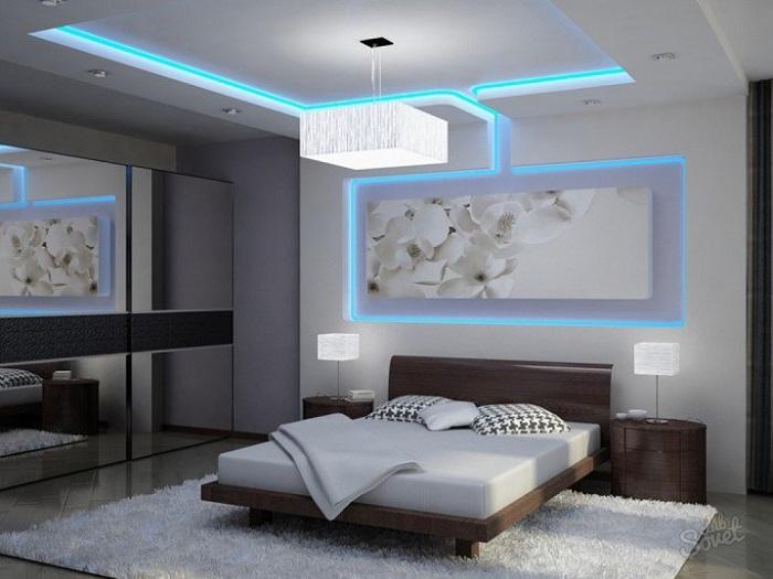 Черно-белая цветовая гамма в спальной обустроена благодаря подсветке.