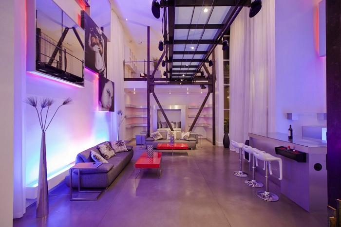 Интересный декор комнаты создан благодаря использованию сиреневых светодиодных ламп.