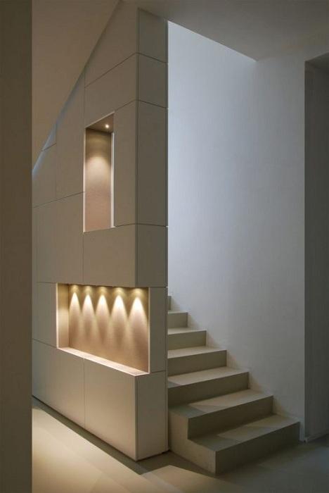 Украшение стены около лестницы при помощи ниш в стене и оригинальной подсветки.