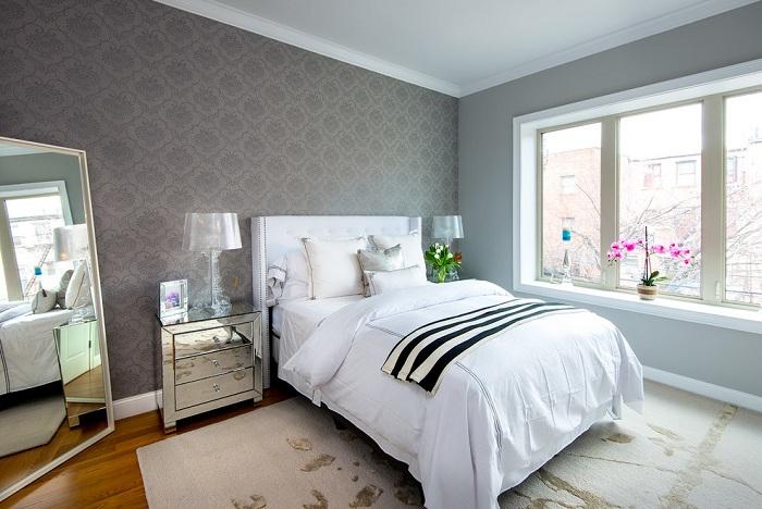 Красивая, но в тоже время не яркая спальня украшена обоями серого цвета с симпатичными узорами.