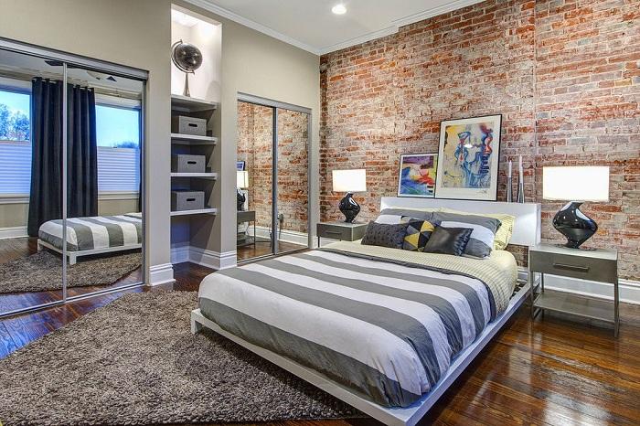 Кирпичная стена — идеальный приём для спален, такой контрастный акцент зрительно расширяет пространство.
