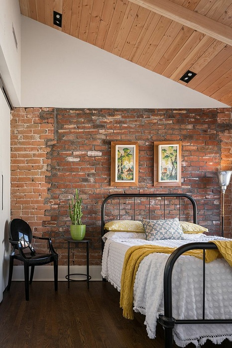 Декорирование стен кирпичом выгодно подчёркивает высокие потолки спальни.