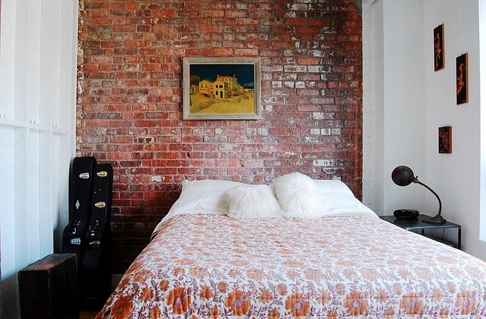 Красивая спальня украшена картинами и каменной кладкой на стене, всё это отлично подчеркивает домашнюю атмосферу.