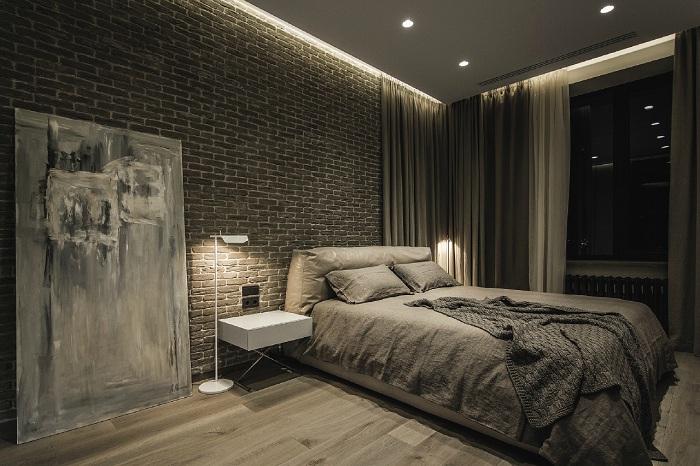 Кирпичная кладка прекрасно гармонирует с дощатым полом и кроватью.
