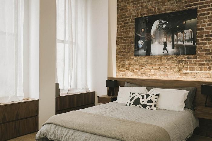 Кирпичная стена в спальне — благодатный фон для необычных картин и постеров.