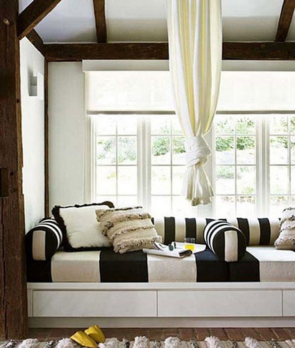 Прекрасное оформление комнаты с чудным диванчиком, который расположился пна подоконнике.