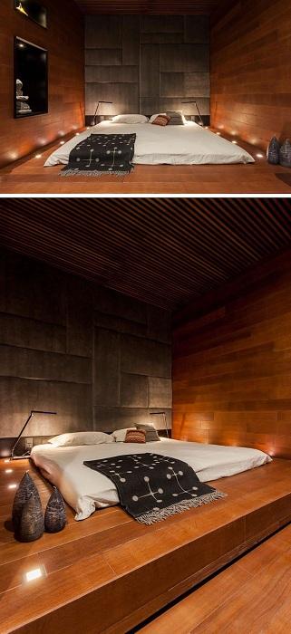 Потрясающий интерьер создан благодаря размещению оригинальной кровати на платформе и удачном выборе освещения.