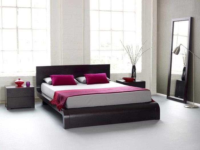 Спальня преображена благодаря размещению оригинальной кровати на платформе плюс ярко—малиновым элементам.