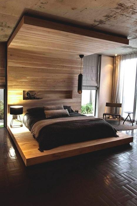 Отменная обстановка в спальной создана с помощью кровати на деревянной платформе.
