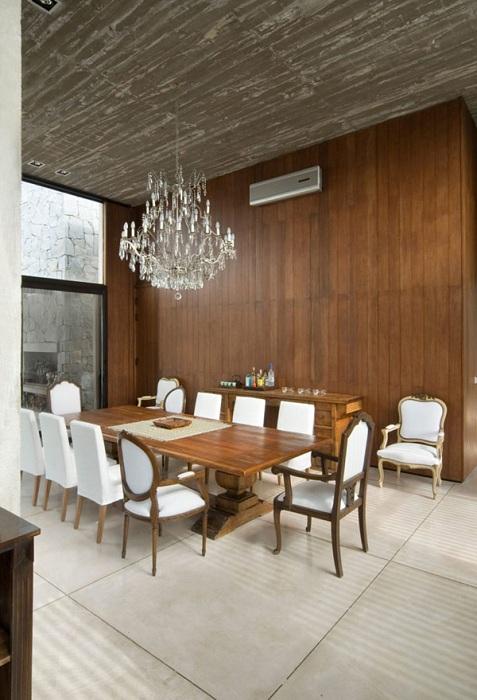 Комната под столовую выглядит чудно из-за деревянной текстурной стены.