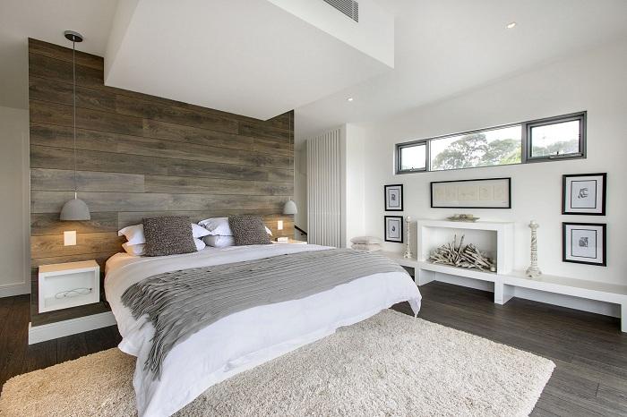Хороший вариант правильно оформить интерьер спальной в серо-белых тонах и деревянной стеной.
