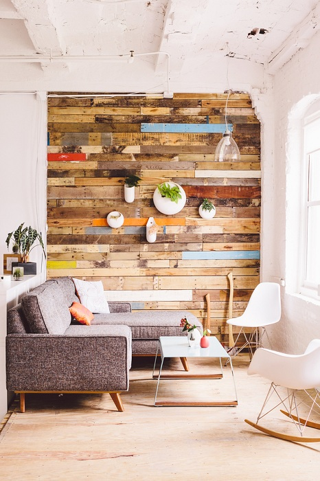 Интерьер гостиной обустроен благодаря нестандартной деревянной стене.