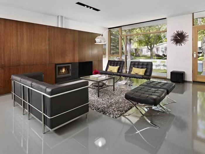 Оригинальный интерьер гостевой комнаты с темной мебелью и деревянной стеной.