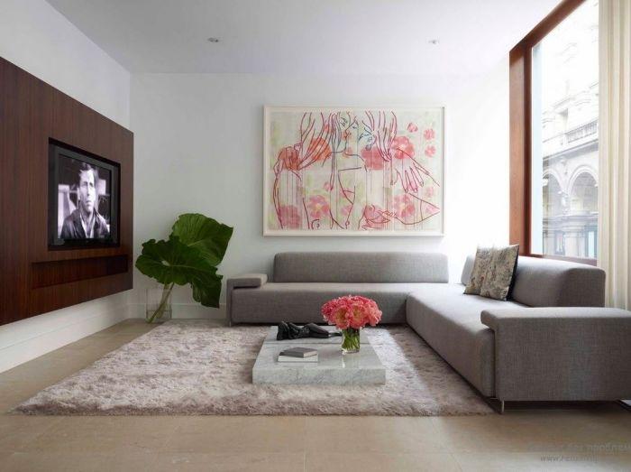 Гостиная комната в минималистском стиле с мягким угловым диваном, небольшим журнальным столиком из декоративного мрамора и шедевром современного искусства.