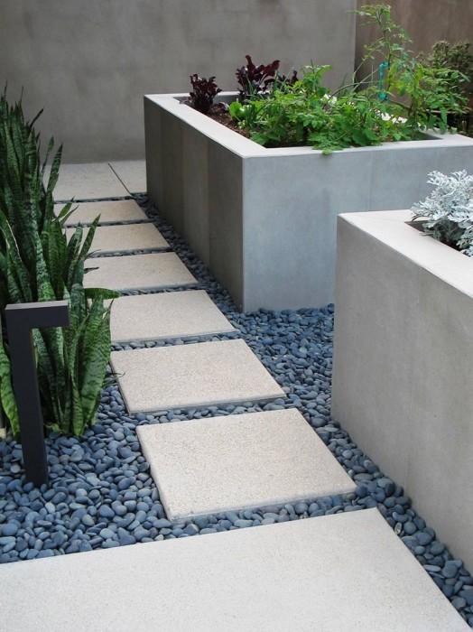 Садовая дорожка из бетона на фоне кремниевой гальки.