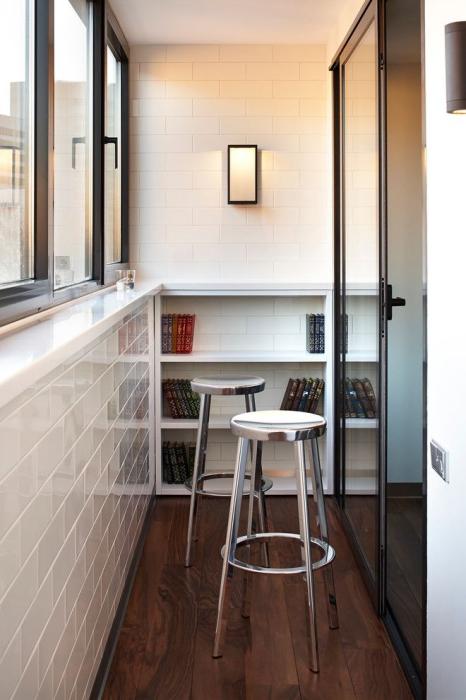 Стильная лоджия с белой кирпичной плиткой, подоконником-барной стойкой, небольшой библиотекой и парой высоких стульев.