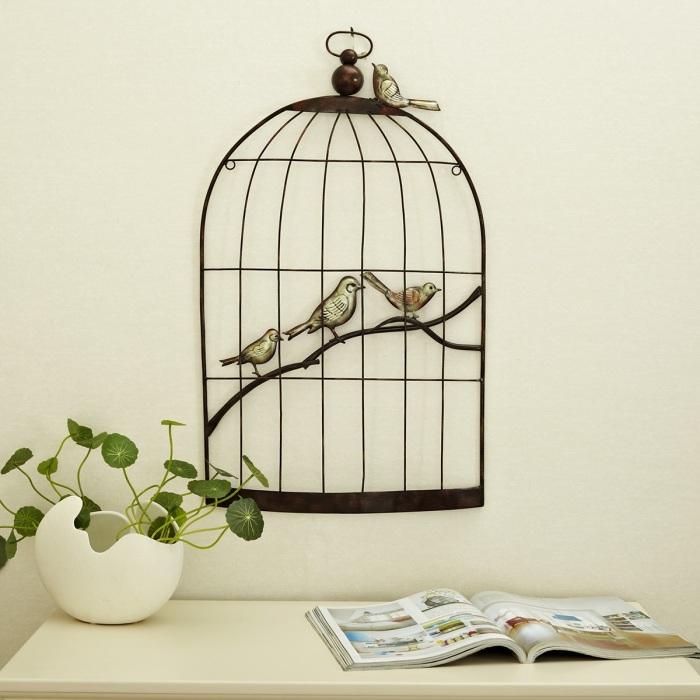 Кованая клетка с птицами стала настоящим произведением искусства.