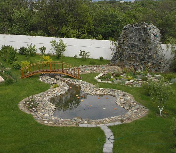 Ландшафтный дизайн садового участка с прудом, классическим водопадом и небольшим деревянным мостиком.