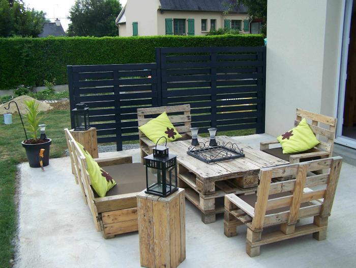 Летнее патио перед входом в дом с практичной и удобной мебелью из деревянных поддонов.
