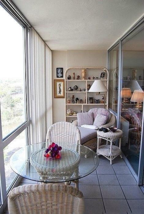 Элегантная лоджия, отделенная от комнаты раздвижной стеклянной перегородкой, с плетённой мебелью, небольшим стеллажом и панельными окнами.
