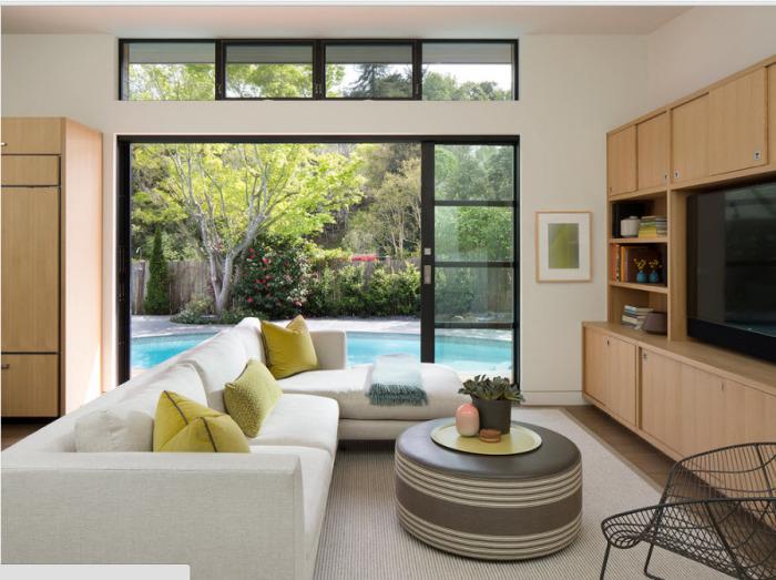 Небольшая гостиная комната с видом на задний двор, в которой можно насладиться вечерней тишиной и умиротворяющим спокойствием воды.