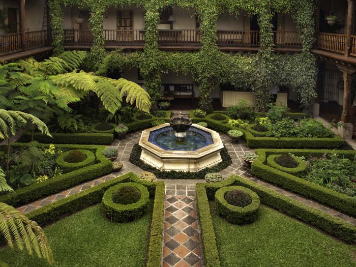 Традиционный итальянский фонтан в форме многогранника в интерьере садового участка.