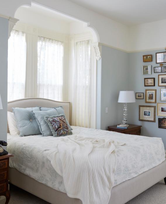 Классическая спальня с необычайно высокими потолками и стенами, которые украшены строгим лепным декором.