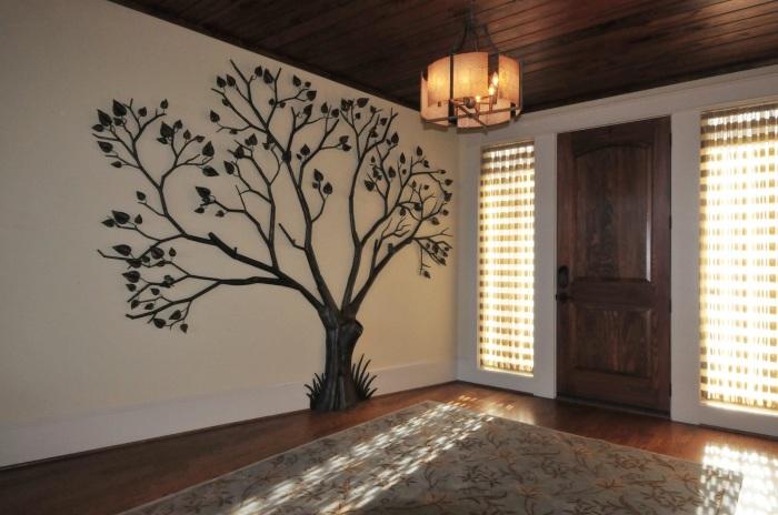 Дерево на стене состоящее из множества кованых элементов.