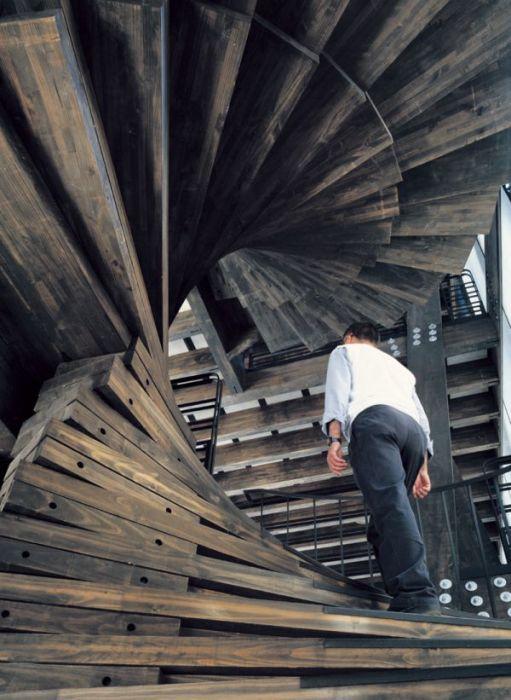 Спиралевидная лестница из темной породы древесины станет ярким акцентом в интерьере загородного дома.