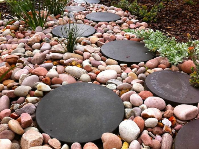 Необычная садовая дорожка из разноцветной гальки и крупных металлических дисков.