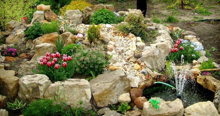 Эффектная альпийская горка с небольшим фонтаном на территории садового участка.