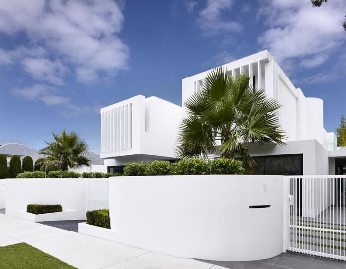 Белый металлический забор, который идеально гармонирует с архитектурным обликом загородного дома.