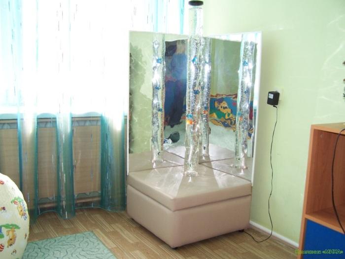 Воздушно-пузырьковая колонна с мягким основанием в углу гостиной комнаты.