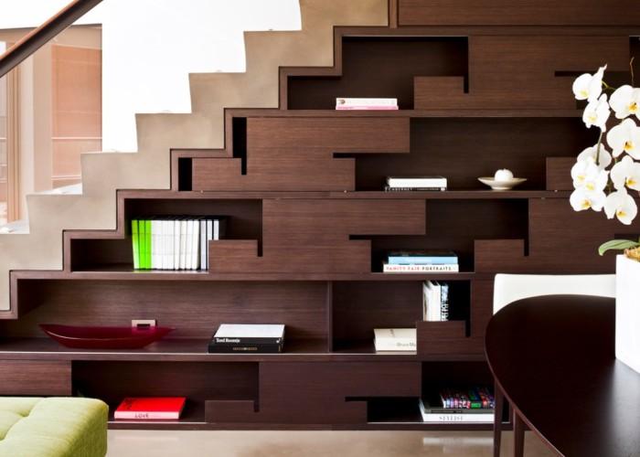 Пространство под лестницей можно заполнить большим стеллажом.