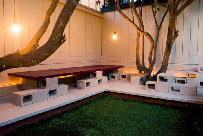 Простая скамейка на территории дачного участка, которую можно создать из нескольких шлакоблоков и деревянной доски.