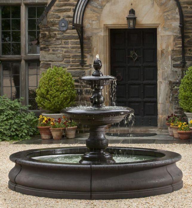 Классический фонтан темного оттенка с круглым бассейном.