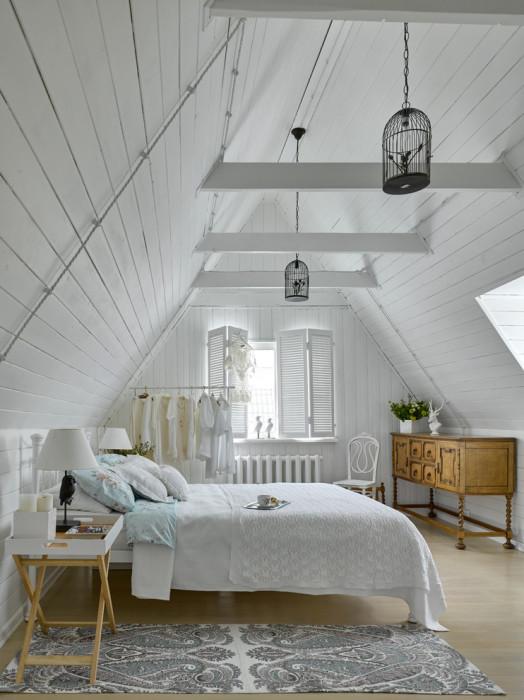 Спальная комната, оформленная в светлых тонах, которые подчёркивают минималистское настроение.