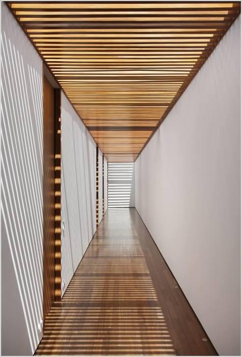 Потолок в коридоре, который благодаря полупрозрачной панели из деревянных реек создает необычную атмосферу.
