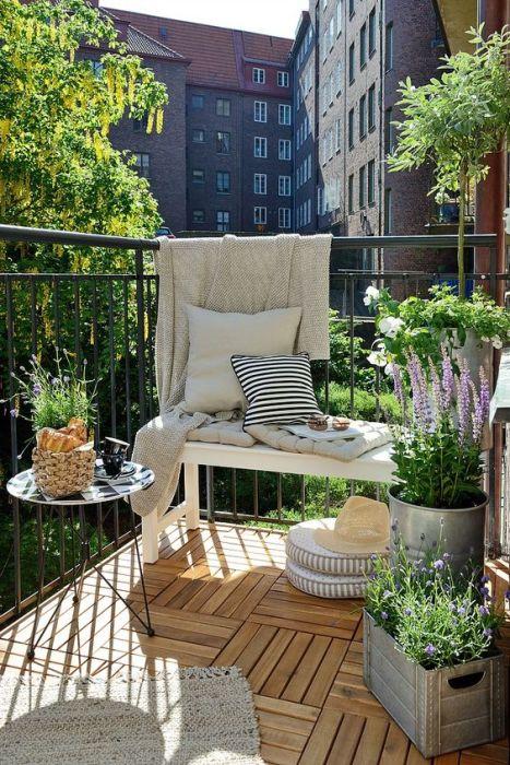 Простенький, но очень уютный интерьер открытой лоджии с небольшой скамейкой, украшенной однотонными мебельными подушками, небольшим кофейным столиком и несколькими самодельными кашпо.