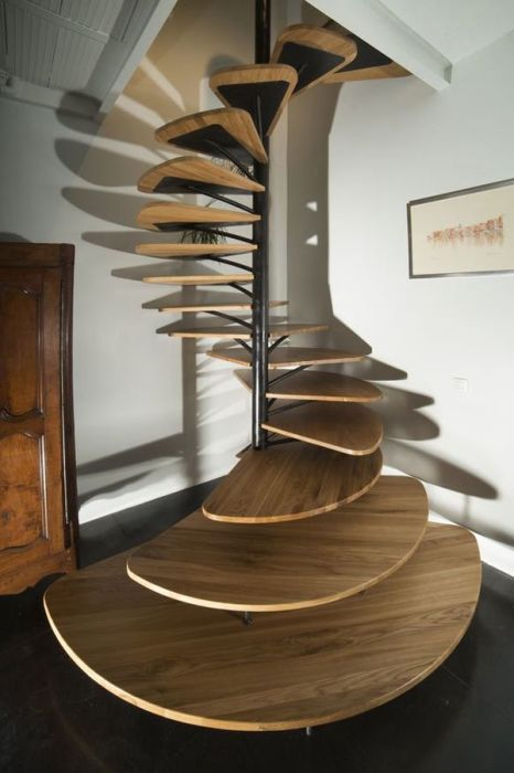 Еще один потрясающий вариант спиралевидной лестницы с единым металлическим каркасом вокруг трубы.