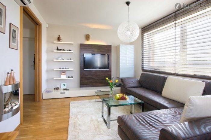 Маленькая гостиная комната с очень практичной мебелью и декором в стиле минимализма.