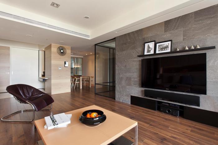 Декорирование стены под телевизор большими каменными плитами.