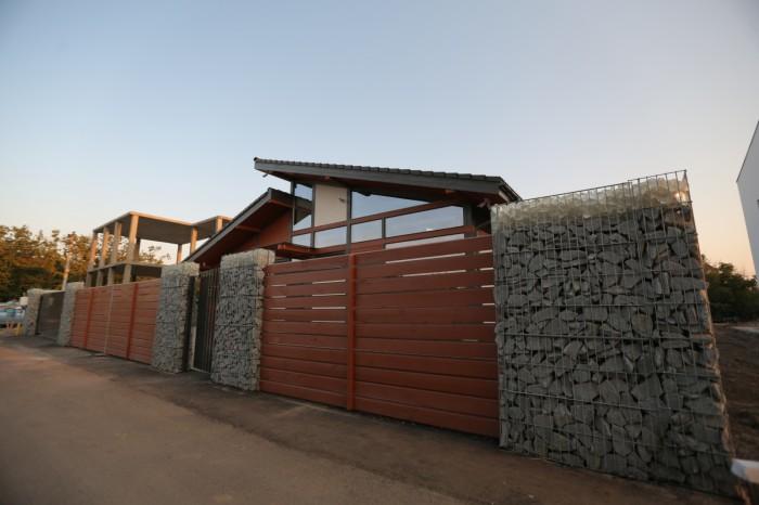 Забор из натуральных камней и светлой древесины смотрится стильно и практично.