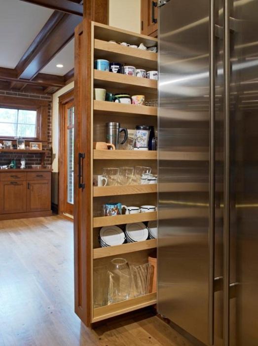 Оригинальный вариант выдвижного стеллажа для кухонной посуды, который придется по вкусу.