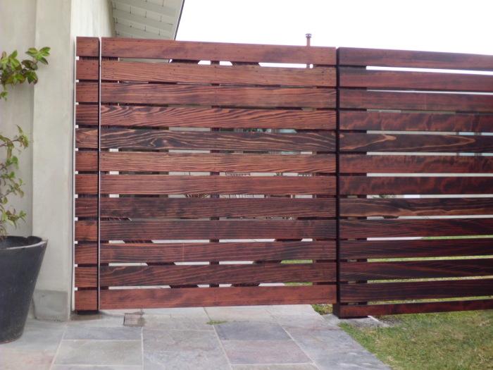 Панельных забор из лакированных деревянных реек - один из самых популярных и доступных способов ограждения загородного участка.