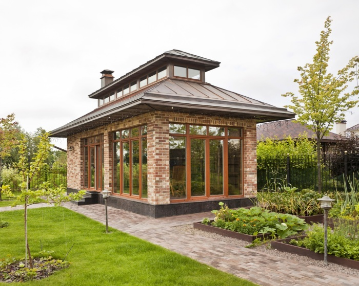 Удобная и практичная беседка на природе в виде маленького дома для садового участка.