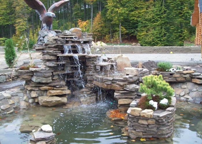 Водопад из натурального слоистого камня с орлом на вершине.